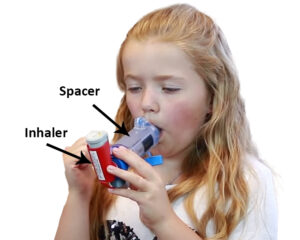 girl using inhaler with spacer